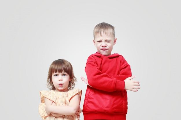 灰色の壁に不満の子供たち。兄と妹はイライラし、怒っています。子供の喧嘩。自己隔離クランチンの状態における子供のストレス。