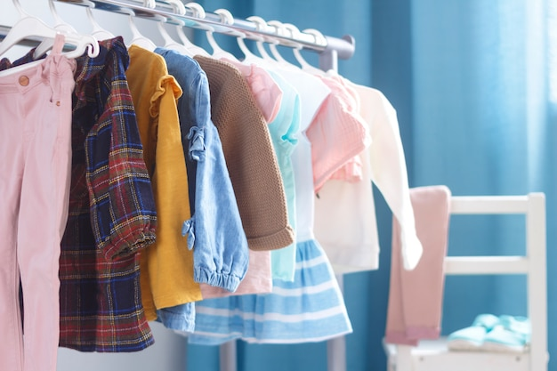 室内のオープンハンガーに並んでいるパステルカラーの子供服。子供部屋には小さな女性用の洋服がありました。