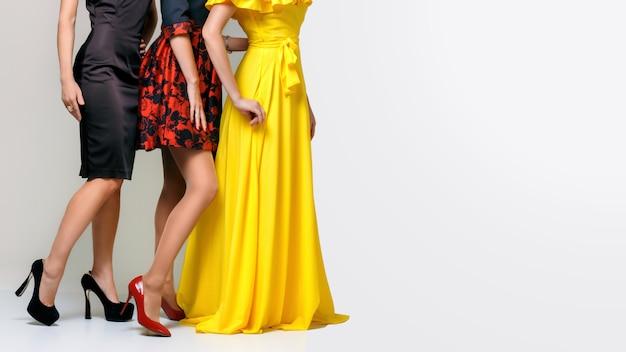 Красивые ножки трех элегантных красивых женщин, одетых в платья и туфли на высоком каблуке