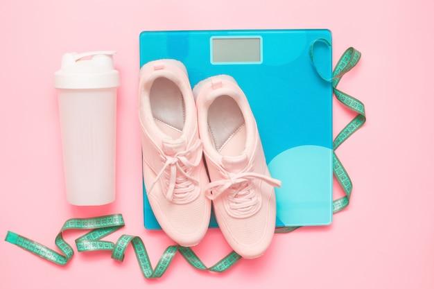 スポーツ用品-ランニングシューズ、体重計、測定テープ、プロテインプラスチックシェーカー。