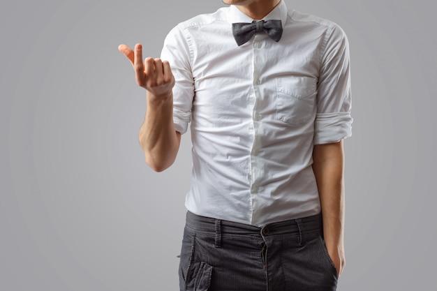 Стильный парень в галстуке-бабочке и белой рубашке показывает что-то маленькое по размеру руками.