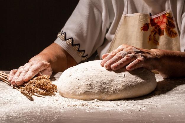 歳の女性、小麦粉のスプラッシュで祖母の手。調理パンは白い粉で覆われたテーブルの上にボール生地を叩きつけます。自然、食品、ダイエット、バイオの概念。テキストのメニューレシピ場所