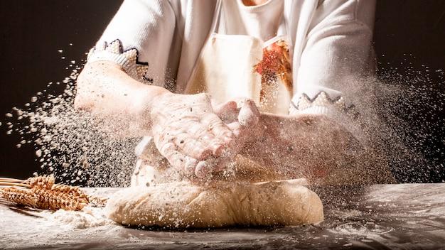 小麦粉のスプラッシュと小麦粉と女性の手の写真。調理パン。生地をこねる。暗い背景に分離されました。テキスト用の空きスペース