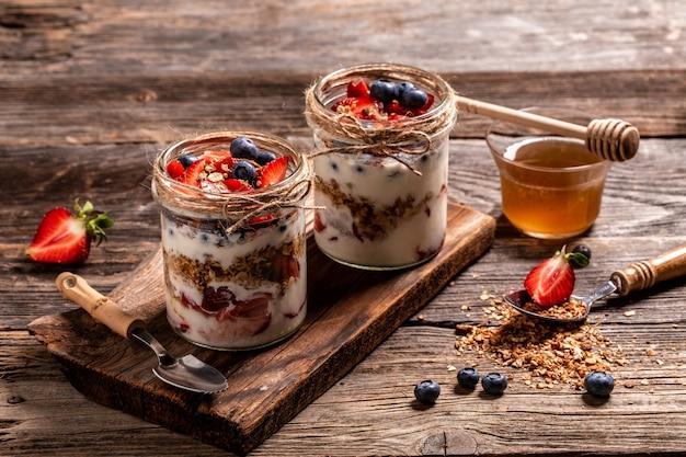 Здоровый завтрак из клубничного парфе со свежими фруктами, йогуртом, медом и мюсли на деревенском фоне