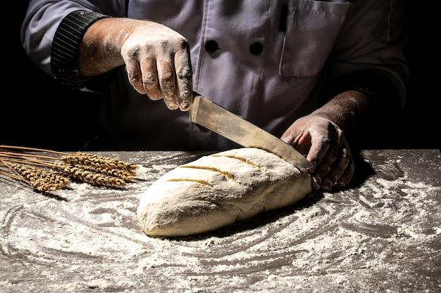 Пекарь, делающий образцы на сыром хлебе, используя нож, чтобы сформировать тесто перед выпеканием