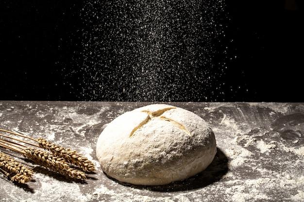 Свежее тесто на доске с колосьями пшеницы