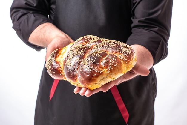 男の手でカラユダヤ人のパン、自家製のベーキング、伝統的なユダヤ人のパン、ユダヤ人のペストリー