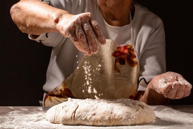 歳の女性、祖母の手伝統的な自家製パンを準備しています。パン生地を混練のビューを閉じます。テキストのメニューレシピ場所