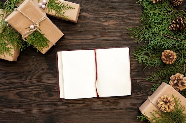Пустая тетрадь, коробки подарков, ветвь и еловые шишки на деревянном. вид сверху