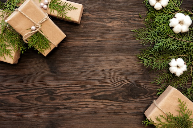 コピースペースと暗い木の板のクリスマスの装飾とギフトボックス