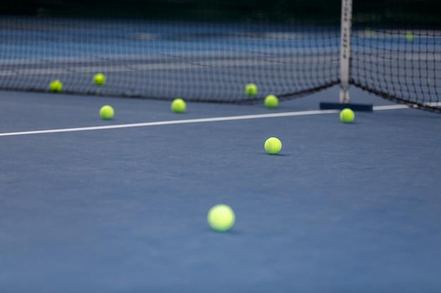 Много теннисных мячей на теннисном корте
