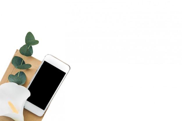 空白の画面と白、トップビューで花と携帯電話。モックアップ