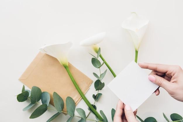 Женские руки держат пустой белый лист на цветы. вид сверху. макет