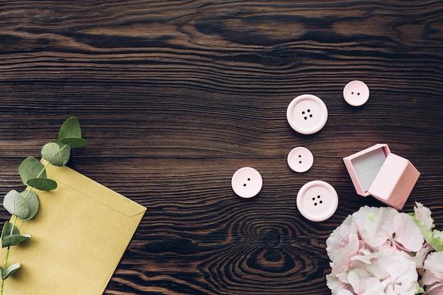 Розовая коробка для обручального кольца, кнопок и гортензии на деревянном столе, взгляд сверху. пространство для текста