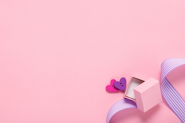 Подарочная коробка и два сердца на розовом
