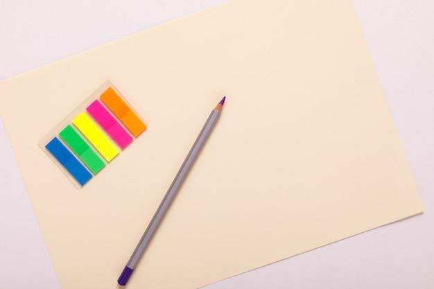 Разноцветные карандаши на разноцветной бумаге, вид сверху