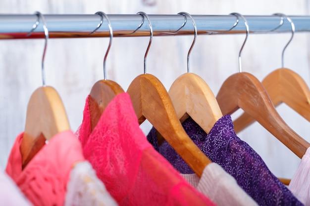 ファッション店のラックのハンガーにピンクの婦人服。クローゼット