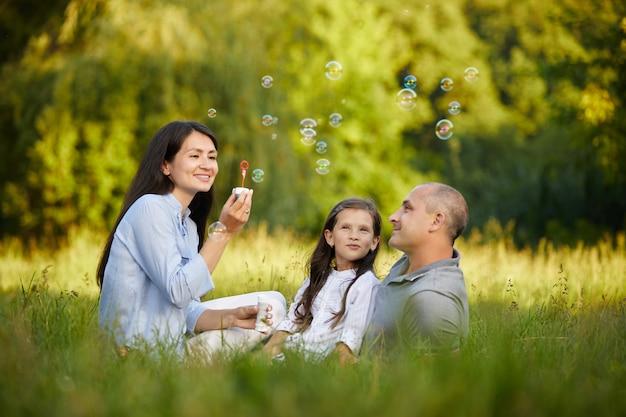 外のシャボン玉を吹く子の女の子と幸せな家庭