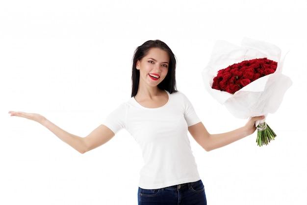 赤いバラの大きな花束を持つ美しい若い女性