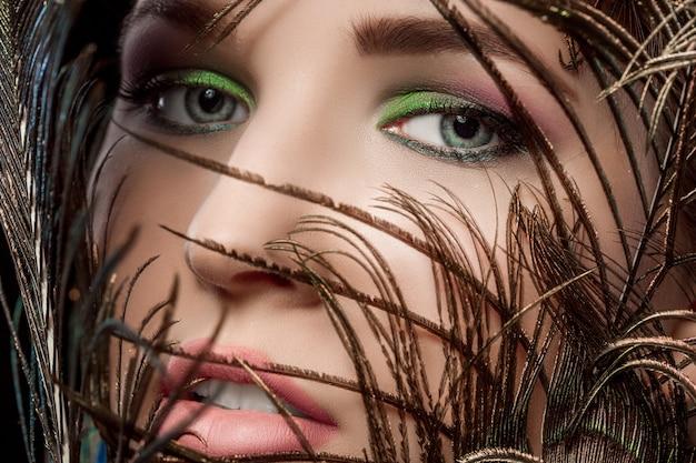 明るい化粧と孔雀の羽を持つ女性