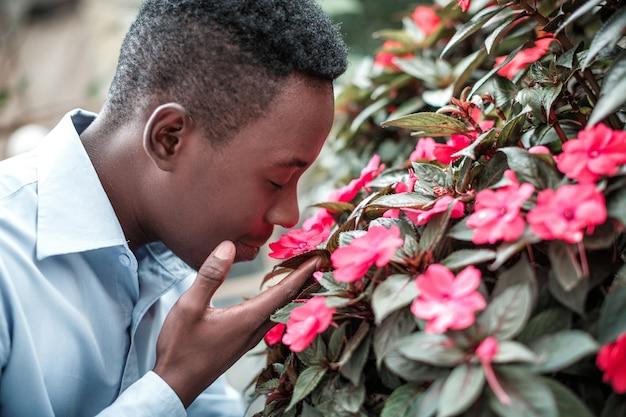 花をくんくんかぐ男