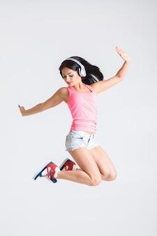 ヘッドフォンで音楽にジャンプする女性