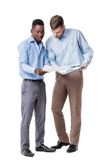 Афро-американский и кавказский бизнесмен, глядя на документы