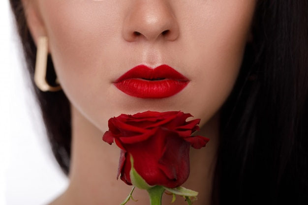 真っ赤な化粧と赤いバラの花を持つ女性の唇。