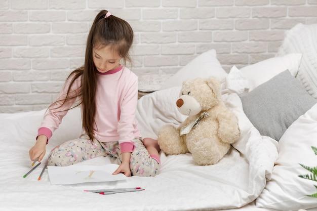 ベッドに横たわっている間絵を描く少女。