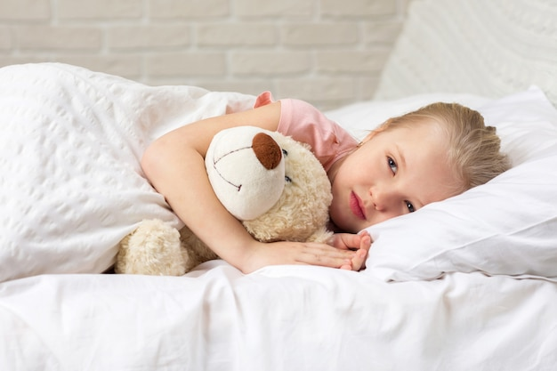 Милая маленькая девочка спит с мишкой