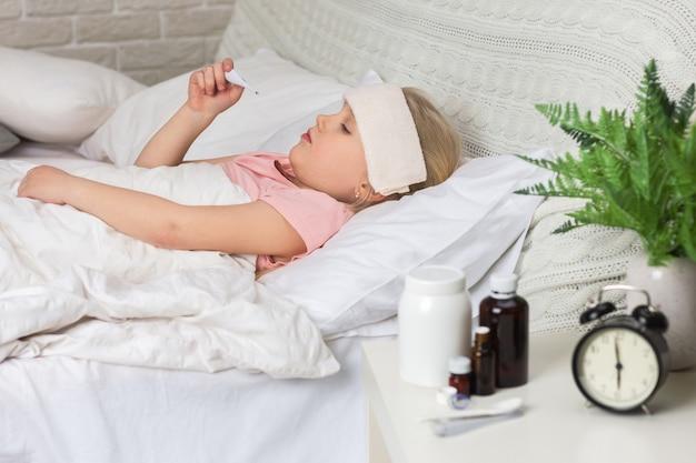 温度計が付いているベッドで横になっている病気の子供女の子。