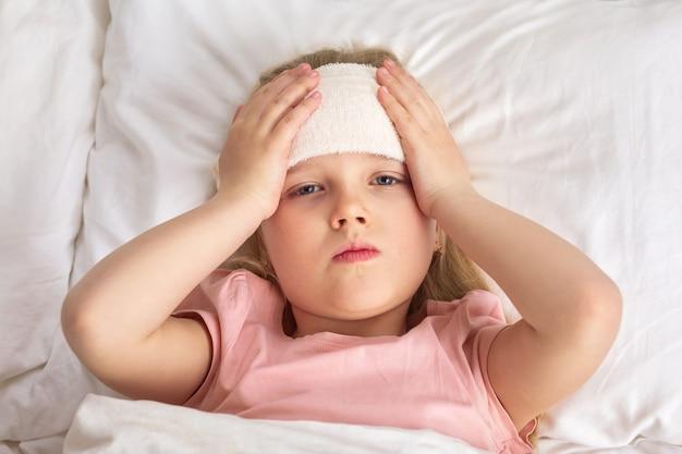 病気の寒い小さな子供の女の子はベッドにあります。