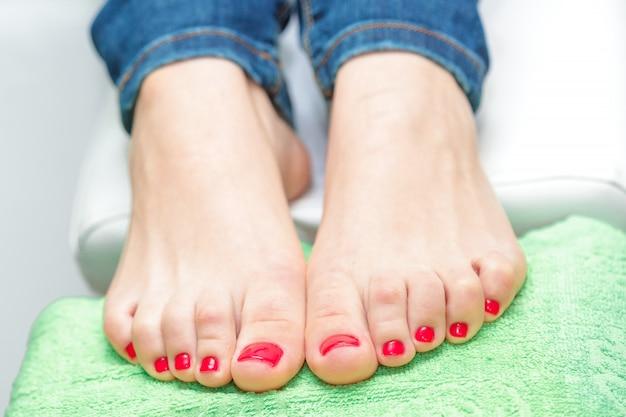 Женские ножки с красным лаком для ногтей