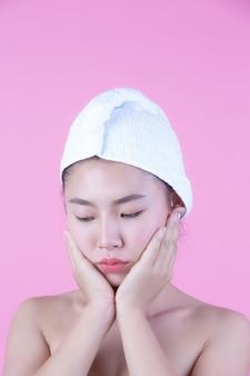 清潔でさわやかな肌を持つ若い女性アジアは自身の顔、表情豊かな表情、美容とスパに触れます。