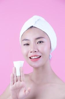 アジアの美しい女性がピンクの背景、美容とスパで顔を拭きます。