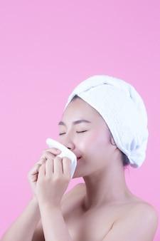 Азиатская красивая женщина, вытирая лицо на розовом фоне, косметология и спа.