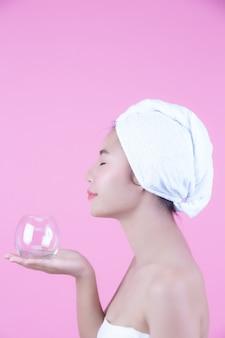 若い女性のフェイスマスクパッドピンクの背景。