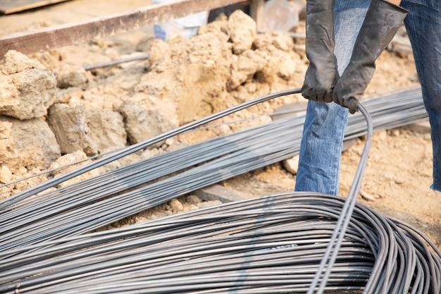 Группа стальных прутков натянута цепью и поднята на стройке