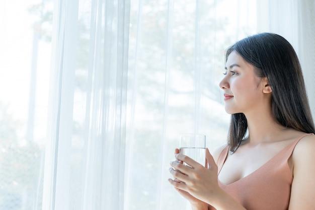 美しい美しさの女性アジアのかわいい女の子は幸せな飲酒を感じます朝の健康のためにきれいな水を飲む