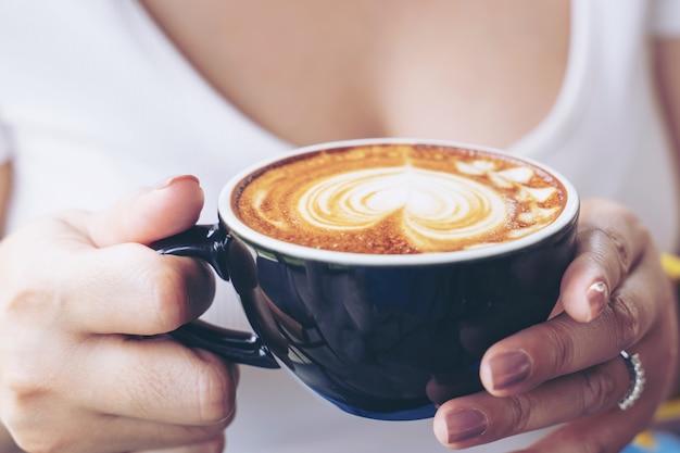 コーヒーショップカフェで女性の手にコーヒーカフェラテアートのカップのクローズアップ