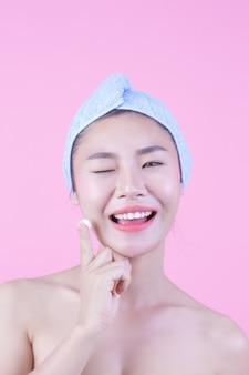 美しい女性のアジアはピンク色の背景に彼女の顔を洗っています。