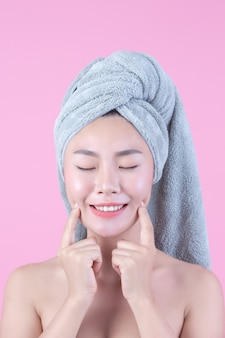 清潔でさわやかな肌を持つ若い女性アジアが自分の顔に触れる