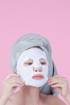 美しいアジアの女性は、ピンクの背景のシートにフェイスマスクを使用しています。