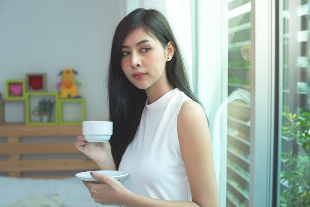 女性は朝コーヒーを飲む