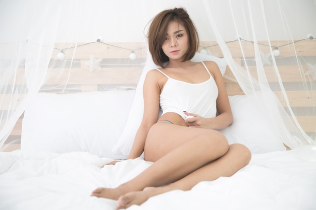 Сексуальная молодая женщина в спальне