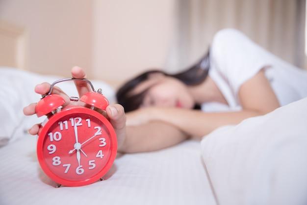 Молодая спящая женщина и будильник в спальне у себя дома