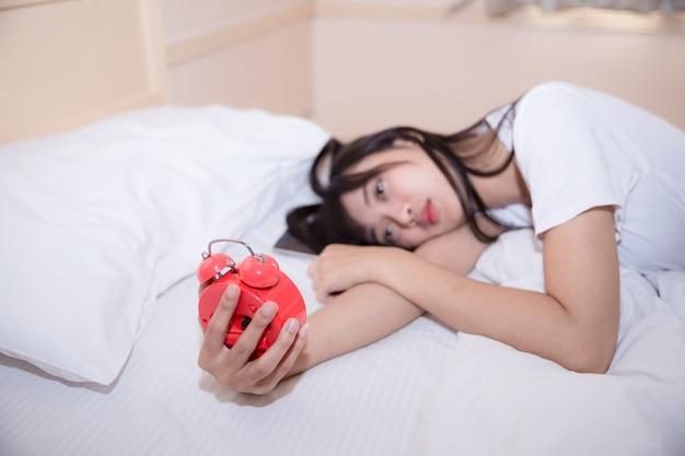 寝ている若い女性と自宅の寝室で目覚まし時計