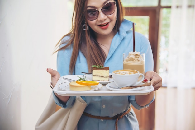 Портрет счастливой молодой азиатской леди в кафе