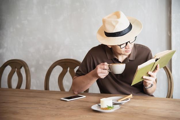 アジア人の男性がコーヒーを飲むと本を読んで