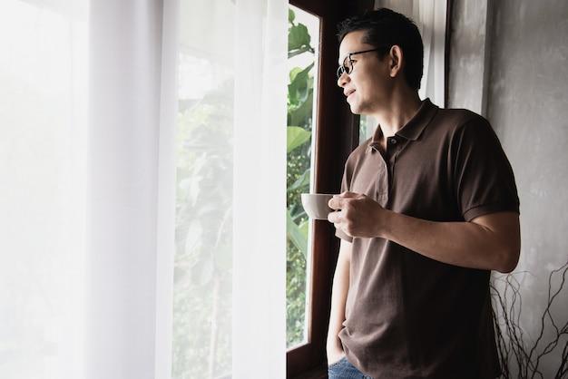 アジア人の男性がコーヒーを飲みながらリラックス